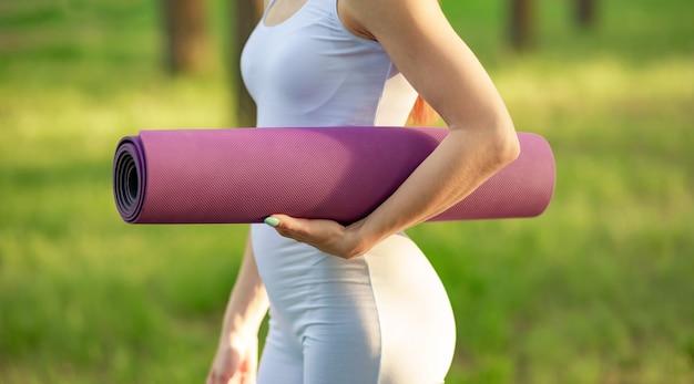 Женские руки разворачивают коврик для йоги перед тренировкой. разрабатывать