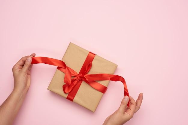 Женские руки развязывают красную ленточку на подарке, завернутом в коричневую крафт-бумагу