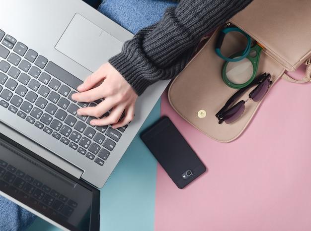 Женские руки используют ноутбук. сумка, смартфон, умный браслет и другие гаджеты и аксессуары. вид сверху