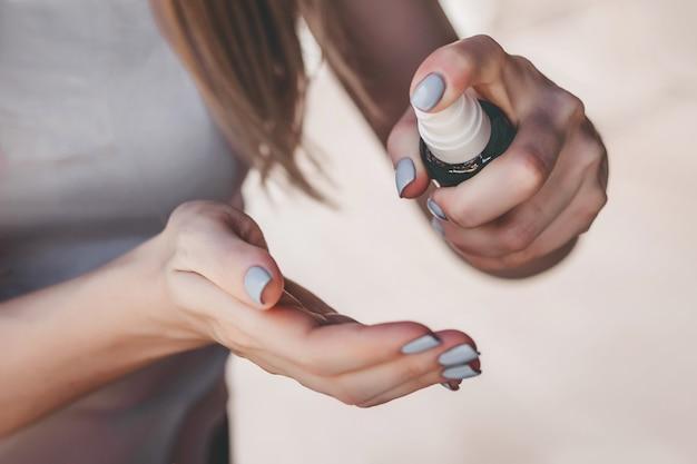 女性の手は消毒スプレーを使用します