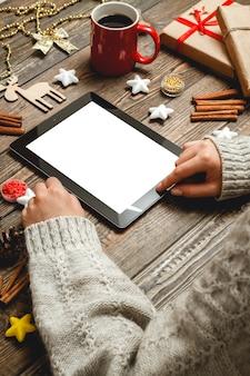 女性の手はタブレットを使用して、クリスマスアクセサリーとテーブルに座っています。