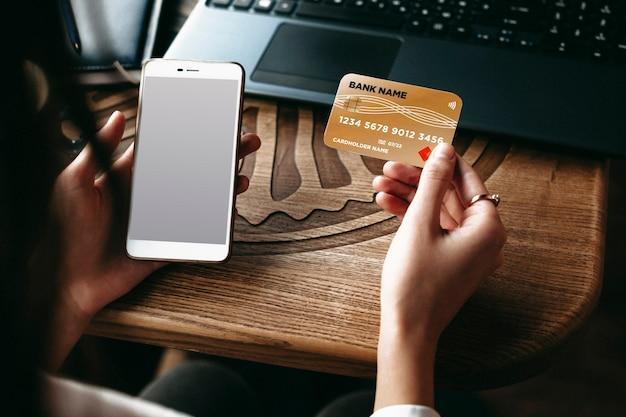 コーヒーショップのテーブルに座ってオンラインで遊ぶためにクレジットカードとスマートフォンを使用する女性の手。