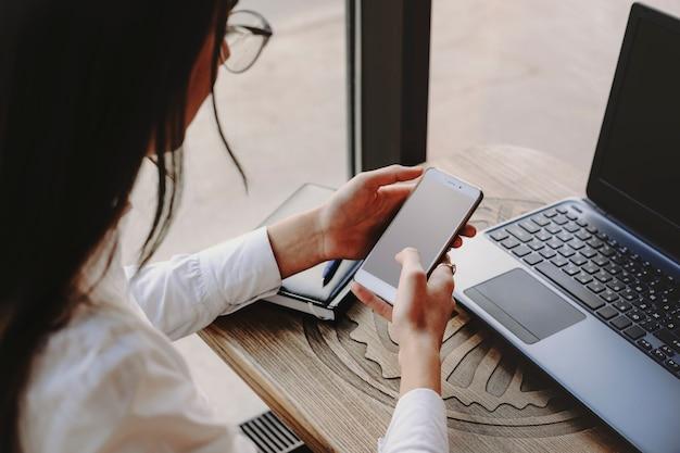 スマートフォンを使用してインターネット取引を操作し、ラップトップをコーヒーショップのテーブルに座っている女性の手。