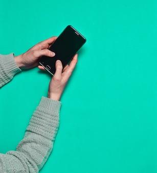 Женские руки, используя смартфон на синей поверхности. вид сверху.