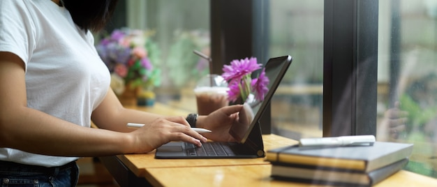 Female hands using digital tablet on wooden table beside window in cafe