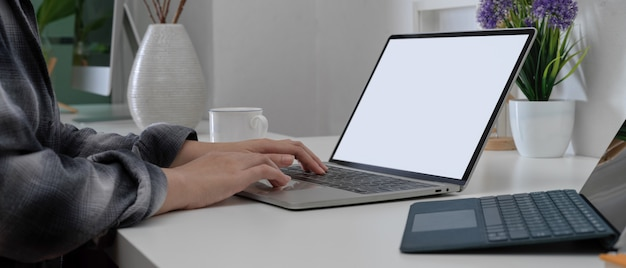 Female hands using mock-up laptop on home office desk