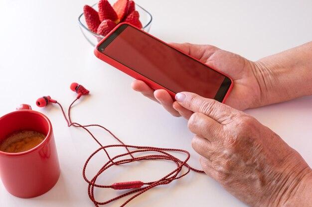Женские руки с помощью телефона с красным экраном. белый рабочий стол с чашкой кофе и клубникой