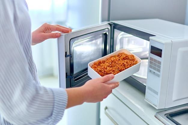 Женские руки разогревают контейнер с едой в современной микроволновой печи для перекуса дома
