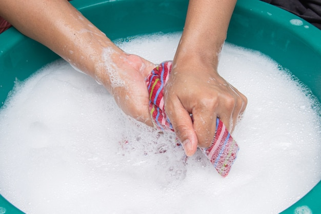Female hands wash clothing by hand with detergent in basin.