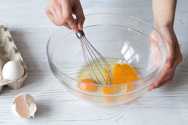 Женские руки взбивают яйца, делают домашние кексы, печенье или торт