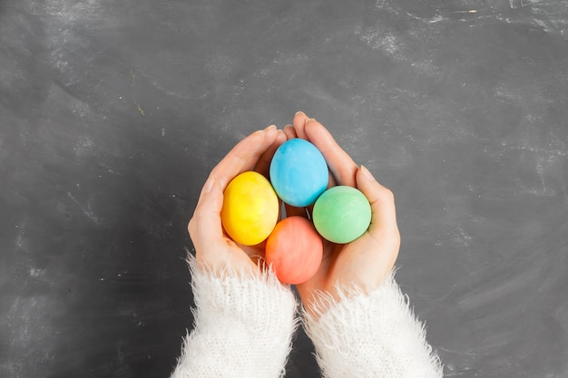 Female hands in a white fluffy sweater hold colorful easter eggs over a chalk board