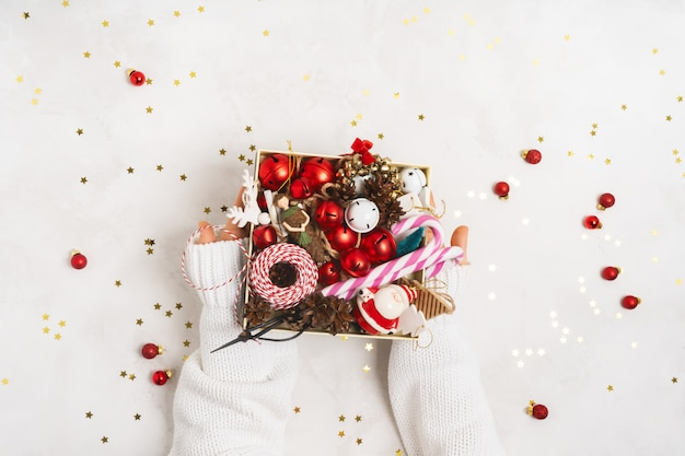 Female hands in white knitted sweater holding a box with vintage christmas props tree toys