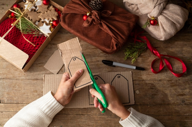 Female hands in a white sweater keep eco frindly packed gift with tags from craft cardboard