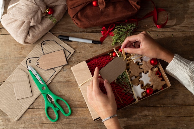 Female hands in a white sweater make gift tags from craft cardboard