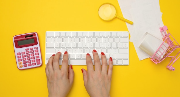 Female hands and white wireless keyboard, stack of paper receipts and magnifier on yellow background, budget analysis concept, savings