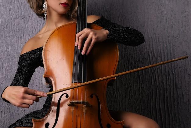 チェロの弦に弓を持った女性の手