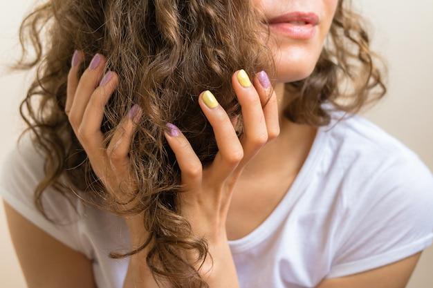 Женские руки с ярко-фиолетовым и желтым маникюром, держащим коричневые вьющиеся волосы