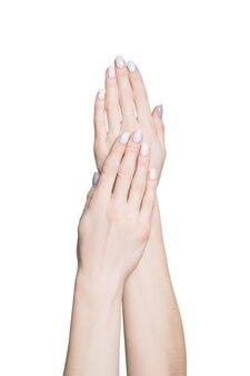 白い表面に優しいマニキュアを塗った女性の手。隔離する