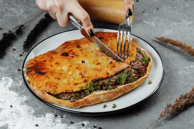Женские руки ножом и вилкой нарезают хачапури с бараниной и чили. грузинская национальная еда.