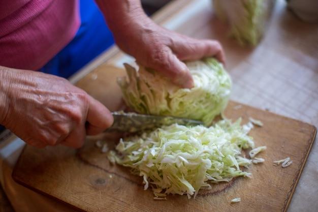 新鮮なサラダを調理するためのナイフチョップキャベツと女性の手