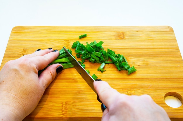 ナイフで女性の手、白い背景の上の木の板に野菜をスライスします。女性はねぎを切る