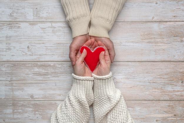 Женские руки с красным сердечком из фетра своими руками лежат в мужских руках