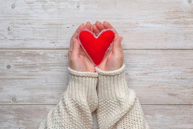 Женские руки с красным сердцем из фетра рукава легкого трикотажного свитера