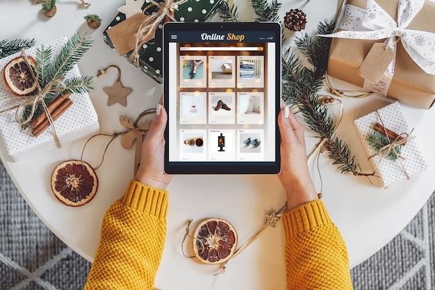 손으로 만든 크리스마스 장식으로 테이블에 태블릿과 여성 손