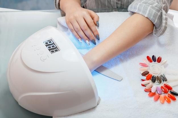 Женские руки с искусственными акриловыми ногтями во время процедуры маникюра клиент сушит ногти в лампе в маникюрном салоне. гигиена и красота рук. цветной лак для ногтей на маникюре в салоне красоты.