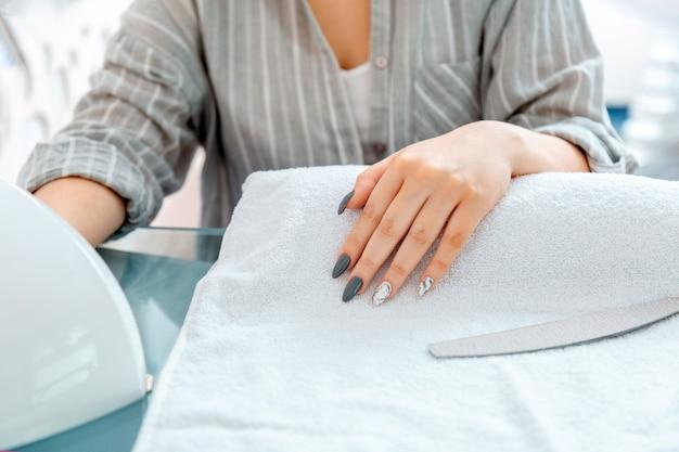 Женские руки с искусственными акриловыми ногтями во время процедуры маникюра. цветной лак для ногтей на маникюре в салоне красоты. клиент сушит ногти в лампе в маникюрном салоне. гигиена и красота рук.