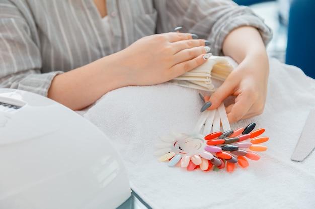 Женские руки с искусственными акриловыми ногтями подбирают новый цвет лака во время процедуры маникюра. цветной процесс лака для ногтей на маникюре в салоне красоты. гигиена и красота рук в маникюрном салоне.