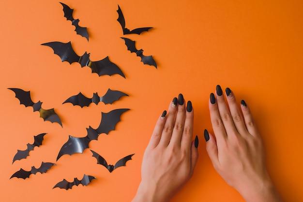 Женские руки с осенним маникюром на оранжевом фоне с летучими мышами. вид сверху. концепция хэллоуина. шаблон оформления салона красоты, социальные сети.
