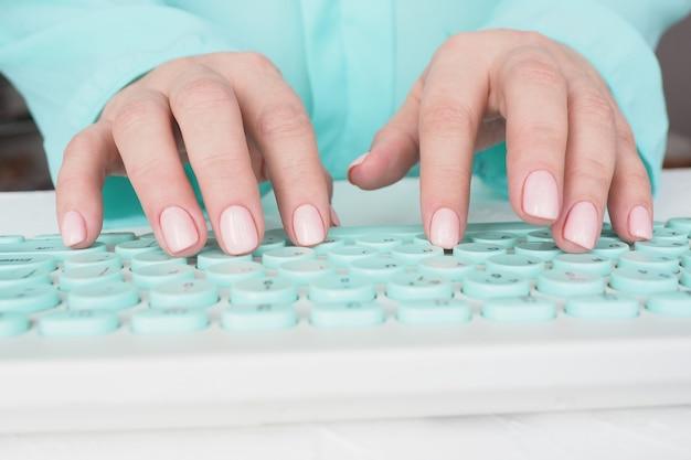 손톱에 아름다운 매니큐어와 부드러운 분홍색 광택이있는 여성 손이 키보드에 입력됩니다.