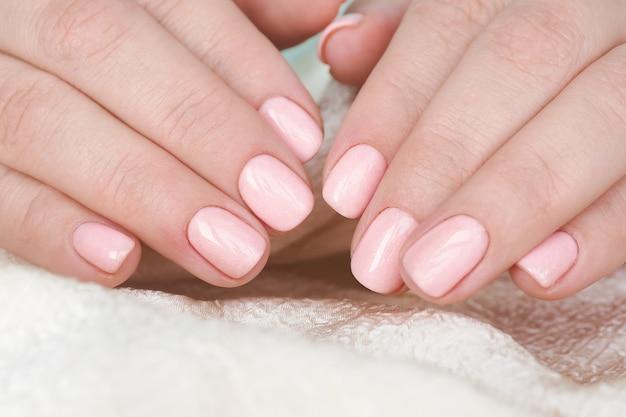 손톱에 아름다운 매니큐어와 부드러운 분홍색 광택이있는 여성 손