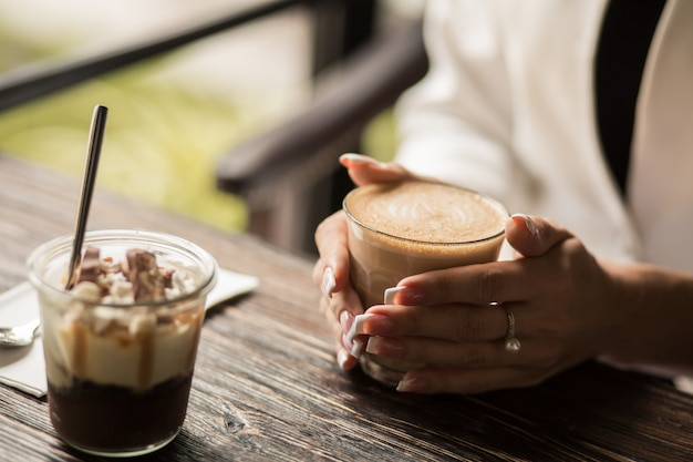 Female hands with beautiful manicure close-up hold a cup with hot coffee on a wooden table