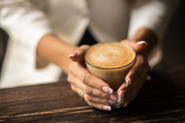 Female hands with beautiful manicure close-up hold a cup with hot coffee on a wooden table.