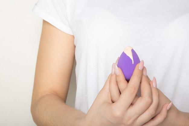 리퀴드 파운데이션이 있는 보라색 뷰티 블렌더를 들고 아름다운 매니큐어를 가진 여성 손