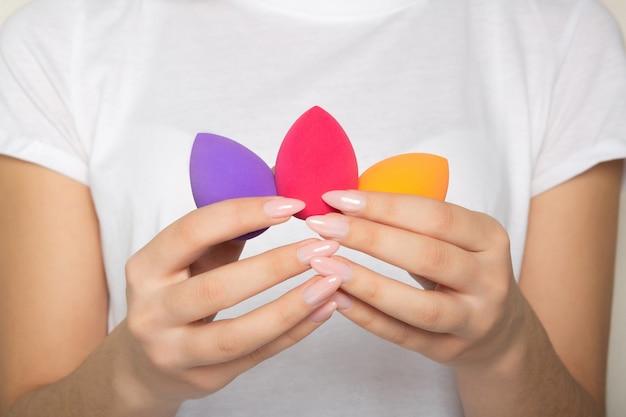 보라색, 분홍색, 주황색 화장품 블렌더를 들고 있는 아름다운 매니큐어를 가진 여성 손