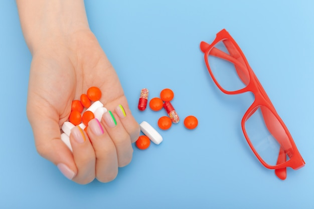Female hands with beautiful modern manicure with pills and glasses