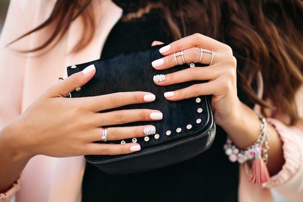 美しいマニキュアと小さな黒い袋を保持しているリングを持つ女性の手。