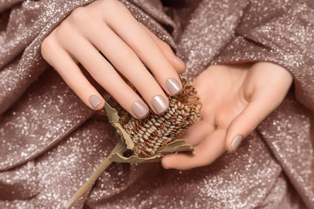 Женские руки с бежевым дизайном ногтей. женские руки, держа коричневый осенний цветок. руки женщины на бежевой предпосылке ткани.