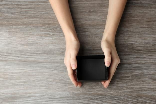 木製のテーブルに黒いオープンボックスと女性の手