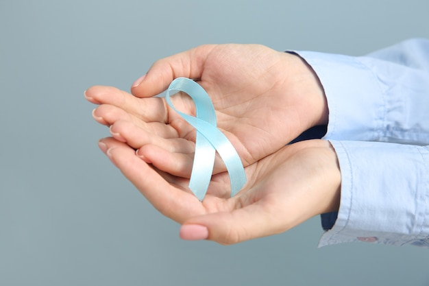 Female hands with blue ribbon on grey. cancer awareness concept