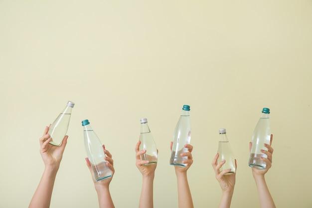 ベージュに水の入ったボトルを持つ女性の手