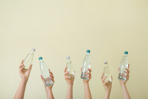 Female hands with bottles of water on beige