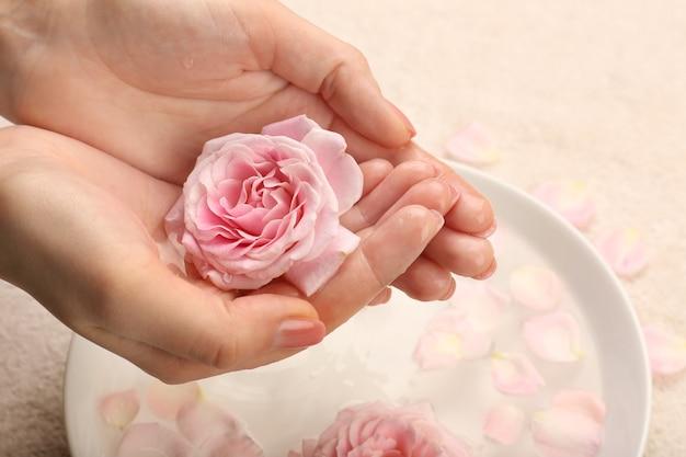 Женские руки с чашей ароматной спа-воды на столе, крупным планом