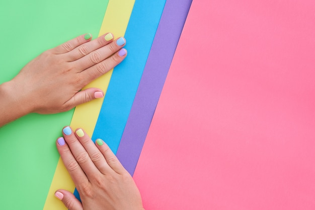 Female hands with bright colors on a colorful background