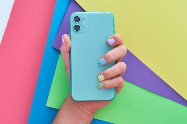 Женские руки с яркими цветами, держа телефон