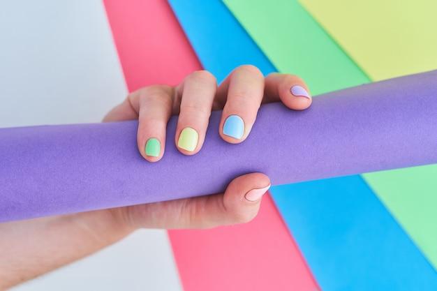 Женские руки с яркими цветами на фоне красочных