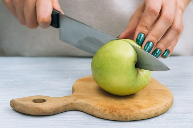 Female hands with a bright manicure cut green apple with a kitchen knife
